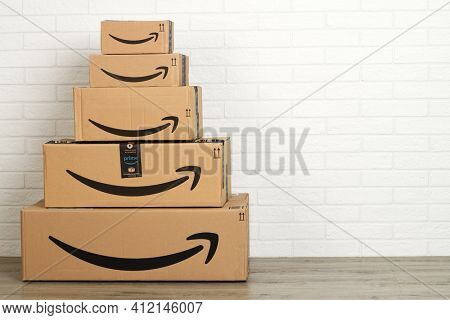 Bergamo, Italy, 5 march 2021: group of Amazon cardboard boxes on white brick wall background.