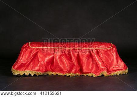 Empty Pedestal Covered With Bright Red Silk Carpet, Golden Fringe On Black Background. Award Ceremon