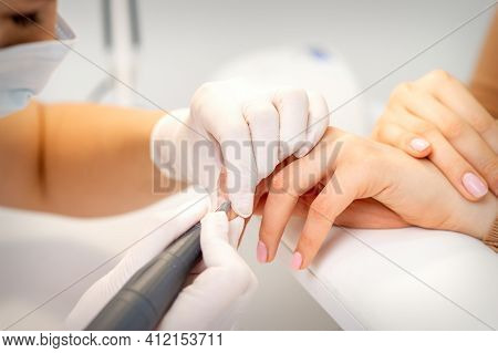 Manicure Master Applying Electric Nail File Machine Removing Old Nail Polish On Fingernails In A Nai