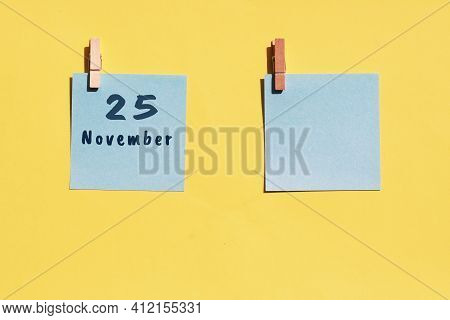 25 November. 25th Day Of The Month, Calendar Date. Two Blue Sheets For Writing On A Yellow Backgroun