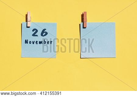 26 November. 26th Day Of The Month, Calendar Date. Two Blue Sheets For Writing On A Yellow Backgroun