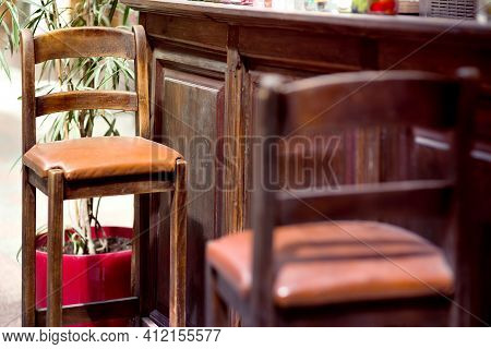 Brown Wood Bar Stool With High Legs And Leather Seat Cushion At The Pub Bar In Retro Style Close-up