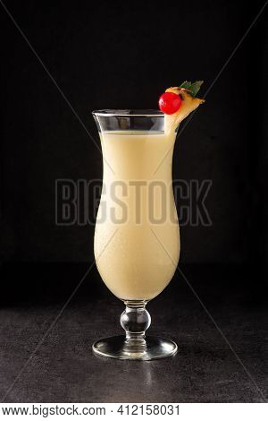 Pina Colada Cocktail Decorated With A Piece Of Pineapple And Cherry On Black Background