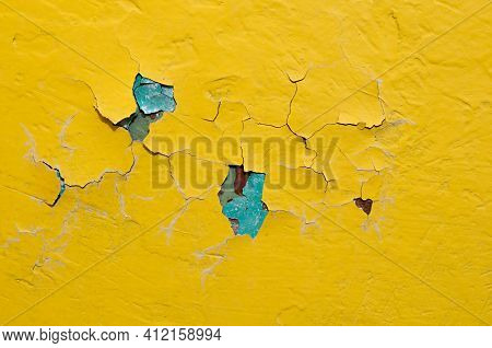 Concrete wall. Peeling paint texture,yellow peeling paint on the concrete background,peeling paint background, fissures on the concrete surface