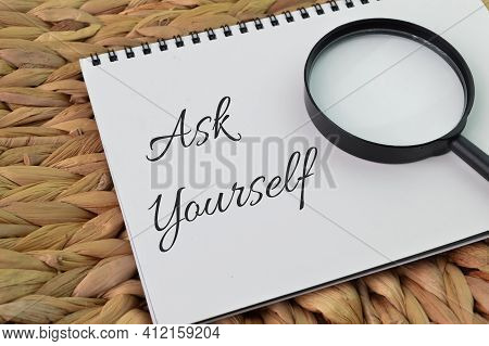 Magnifying Glass And Notebook Written With Text Ask Yourself.
