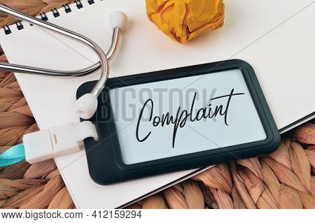 Paper Waste, Stethoscope, Notebook And Name Tag Written With Complaint.