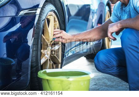 Caucasian Men Washing And Detailing His Exotic Car Alloy Wheels Close Up. Automotive Theme.