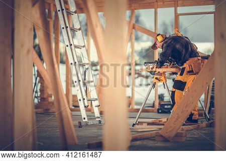 Caucasian Contractor Worker In His 40s Trimming Wooden Elements Using Commercial Grade Powerful Elec