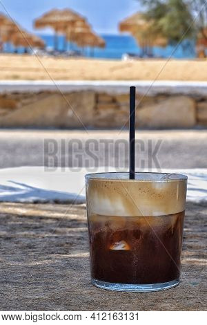 Closeup Of An Iced Coffee With A Straw In Front Of The Mylopotas Beach In Ios Greece