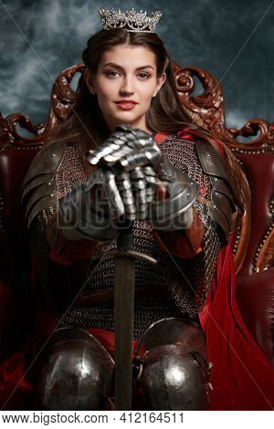 Portrait of a beautiful medieval queen in knightly armor sitting on a throne and holding a sword. History of the Middle Ages.