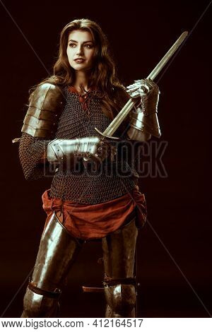 A brave noble warrior woman in chainmail and plate armor poses holding her sword. Medieval knight. Studio portrait on a black background.