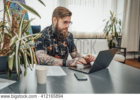 Cosy Home Office And Remote Working. Man With Beard And Tattooed Body Wearing Stylish Clothing Doing