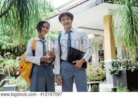 Couple Of High School Students Stand Smiling At The Camera While Wearing A Bag And Carrying A Laptop