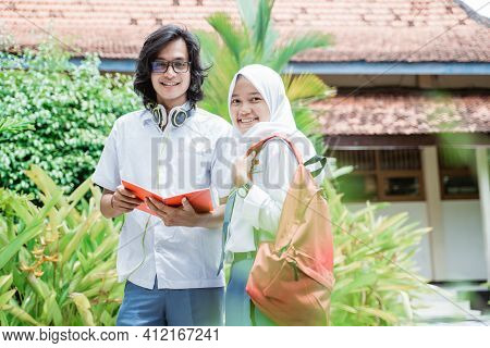 High School Boy Wearing Glasses And Headphone Holding Book With Veiled Female Students Standing Smil