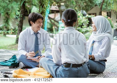 Three Teens In High School Uniform Discuss Group Assignments Sitting On The Floor