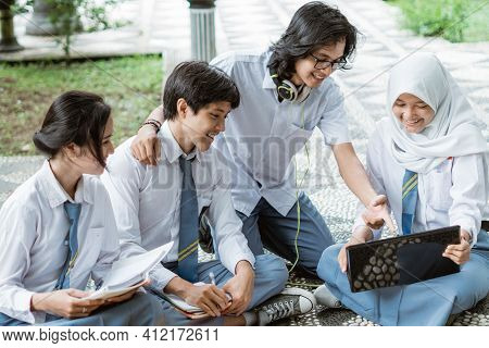 Four Teens In High School Uniform Use A Laptop Doing Group Assignment Sitting