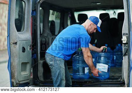Delivery Man In Front Cargo Van Delivering Bottles Of Water.