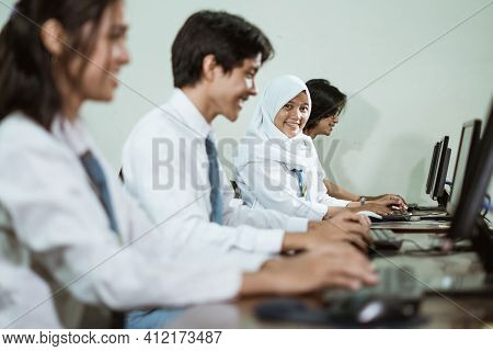 Indonesian High School Students Using Computer Pc With Their Friends Studying In A Computer Lab Room
