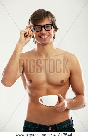 Funny portrait of young naked man with cofee and newspaper isolated over white background