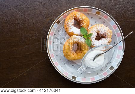 Donuts On The Plate. Three Donuts With Powdered Sugar, Mint Leaf And Sour Cream On The Plate. Wooden