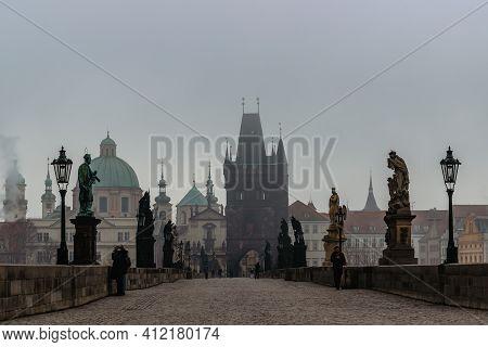 Prague, Czech Republic - February 24, 2021.view Of Charles Bridge, Old Town Bridge Tower In Cold Fog