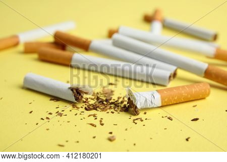 Broken And Whole Cigarettes On Yellow Background, Closeup. Quitting Smoking Concept