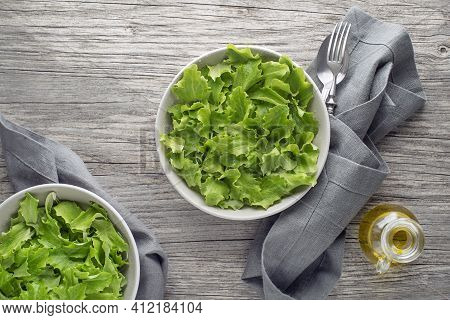 Healthy Green Lettuce Salad On Wooden Table Background. Freshly Picked Of Young Green Leaves
