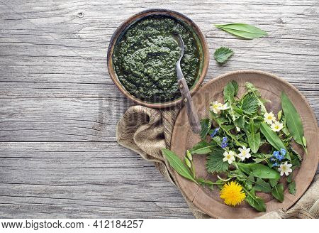 Healthy Soup With Fresh Spring Ingredients. Dandelion, Wild Garlic, Flowers And Nettle Leaves On Woo