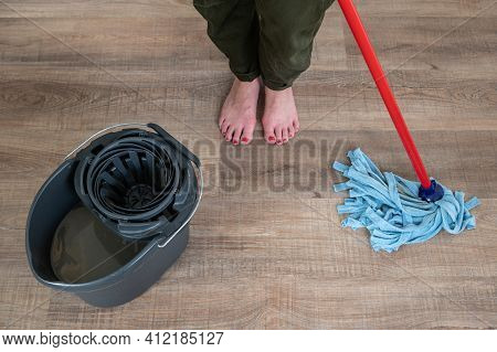 Close Up Of Young Barefoot Woman With Red Painted Nails Scrubbing A Wooden Floor.top View.