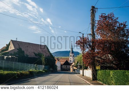 Main Street With Rorschwihr Village In Alsace With Mountains And Eglise Saint-michel Church In Backg