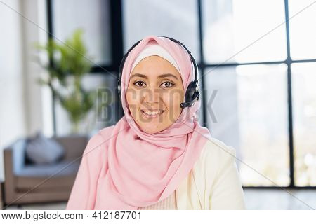 Headshot Of Young Muslim Arab Mixed-race Woman In Hijab And Headset Sitting In The Office With Panor