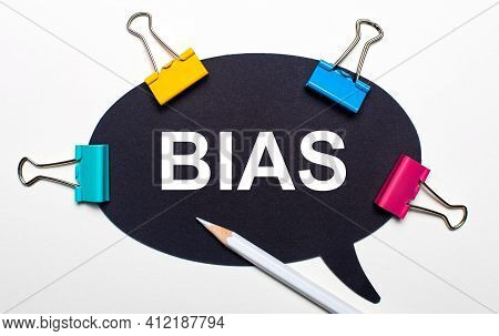 On A Light Background, Multi-colored Paper Clips, A White Pencil And Black Paper With The Words Bias