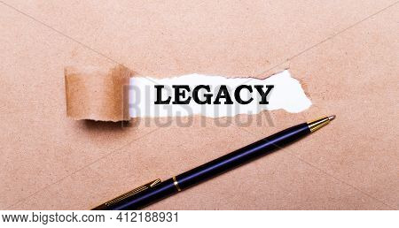 Torn Kraft Paper, White Background With The Text Legacy. Nearby Is A Black Handle. View From Above