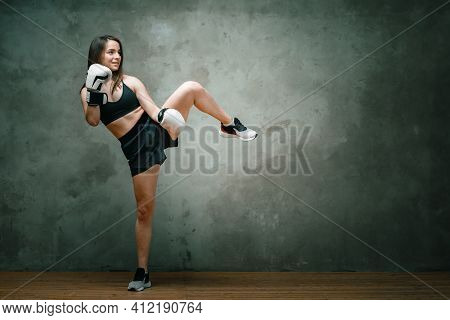 Young Athletic Woman Boxer In Shorts, Short Top And Boxing Gloves Doing A Kick Above His Head On Dar
