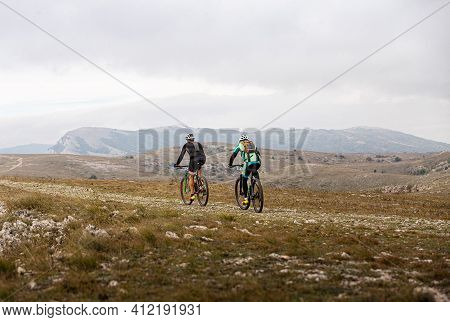 Two Male Cyclists Riding On Mountain Road On Mountain Bike
