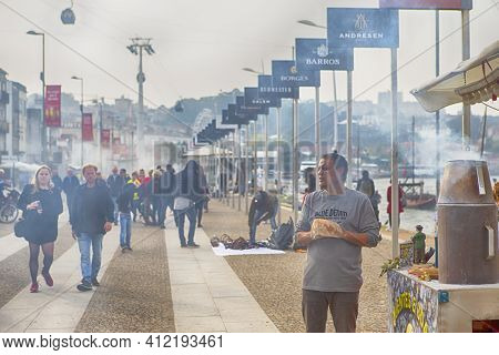 Porto, Portugal - October 26, 2018: Male Street Vendor Selleing Traditional Grilled Chestnuts At Por