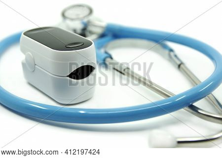 Stethoscope And Pulse Oximeter Isolated On White Background. Pulse Rate Health Tester Is Used To Mea