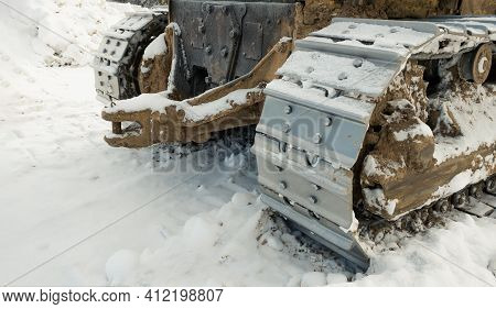The Metal Tracks Of A Bulldozer Tractor In Winter Clears The Road From Snow. On A Frosty Day, A Yell
