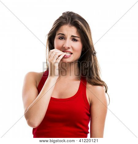 Beautiful young woman biting her nails, isolated over a white background