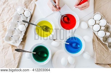 Flat Lay. Dyeing Easter Eggs With Liquid Food Coloring. Different Colors In Different Bowls