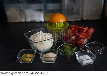Ingredients For A Dessert With Double Cream Cream Cheese, Strawberries, Chopped Pistachios, Sugar, O