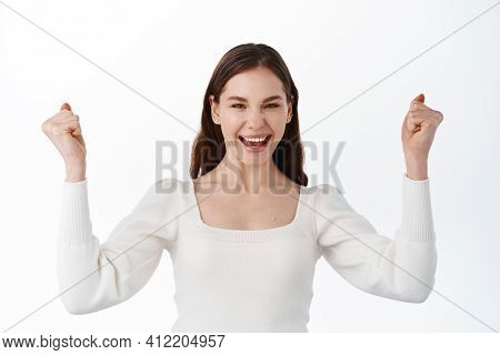 Image Of Excited Young Lady Standing Isolated Over White Background Make Winner Gesture. Girl Winnin