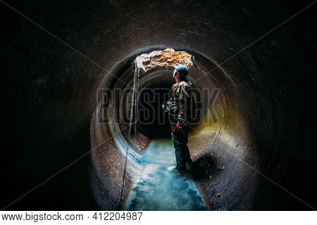 Sewer Tunnel Worker Examines Sewer System Damage And Wastewater Leakage.