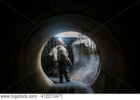 Sewer Tunnel Worker Examines Sewer System Damage And Wastewater Leakage