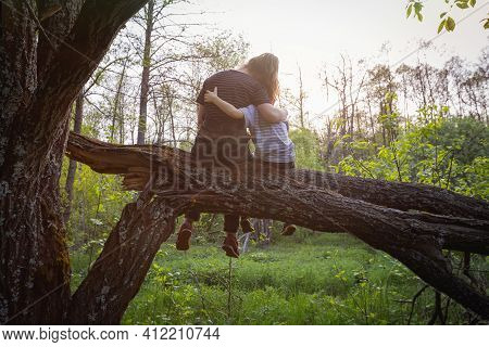 Relationship Of Loving Mother And Little Son Sitting In Tree While Walking Through Spring Forest. Fr