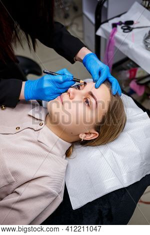 A Make-up Artist Applies A Sketch To The Eyebrows Of A Young Girl With An Eyebrow Pencil. Profession
