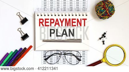 Notebook With Repayment Plan Word With Office Tools On White Table.