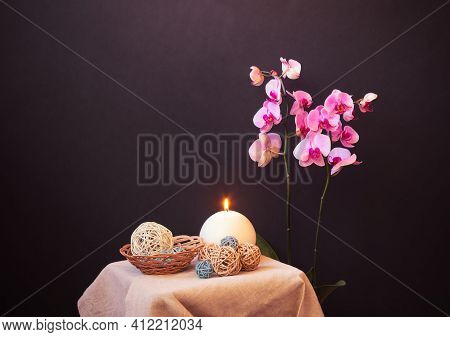 Purple Orchid, Candle And Decorative Balls Near On Dark Background. Relax And Spa Concept. View With