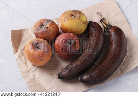 Spoiled Rotten Foods With Mold: Apples And Banana On Gray Background. Close Up.