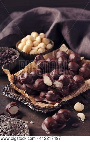 Chocolate and macadamia clusters on a dark background